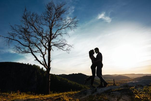 愛のカップルのシルエット。男と女の日没で抱き締めます。カップルが旅行します。自然の中の恋人。男と女が夕日を見て。日没時の恋人。山を旅します。新婚旅行