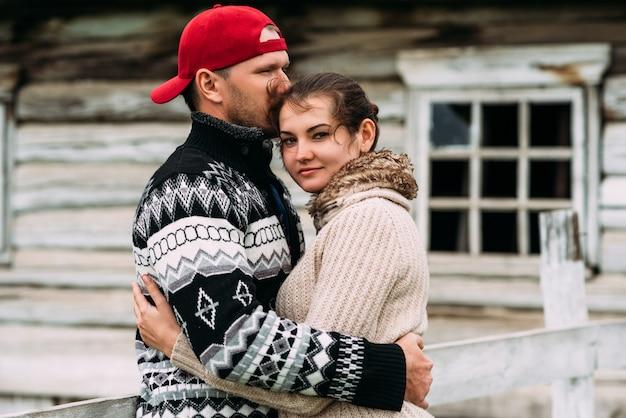 女性と男性の愛と関係。若い家族の概念。愛のカップルが抱擁します。男性が女性にキスします。屋外で幸せなカップル。村の若いカップル
