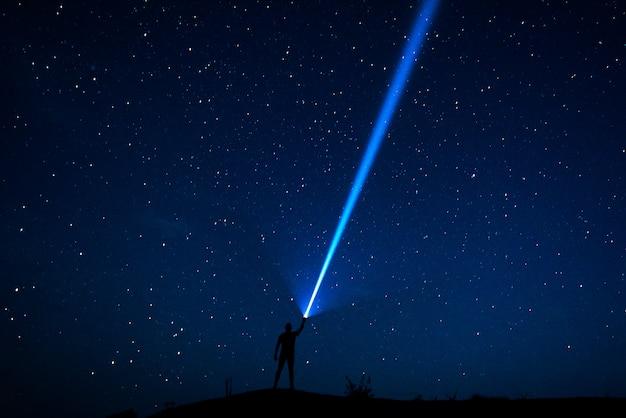 空の星。旅行者は星空を見ます。星と腕を上げた男のシルエットと夜空。ランタンを持つ男。強い光のビーム。強力な懐中電灯