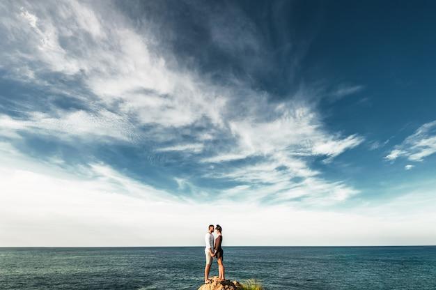 海沿いの愛のカップル。海沿いの幸せなカップル。カップルは世界中を旅します。アジアを旅する男女。新婚旅行。海ツアー。美しいカップルはビーチで夜明けを満たしています