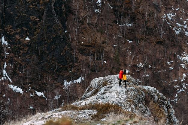 山を旅行する愛のカップル。男と女の旅行。山で休んでいるカップル。山に登る。山でのハイキング。