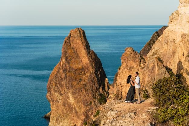 崖の端で抱き締める海沿いの愛のカップル。男は女の子に提案します。山での新婚旅行。男と女の旅行。結婚式。旅。愛。海で休んでいる新婚夫婦