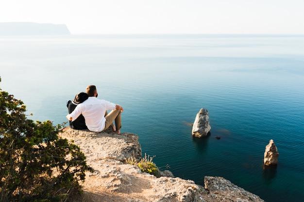 海沿いの崖の端に座っている男女。ハネムーン。新婚旅行。海の男と女。男と女の旅行。カップルが抱擁します。カップルがキスします。新婚カップル。恋人
