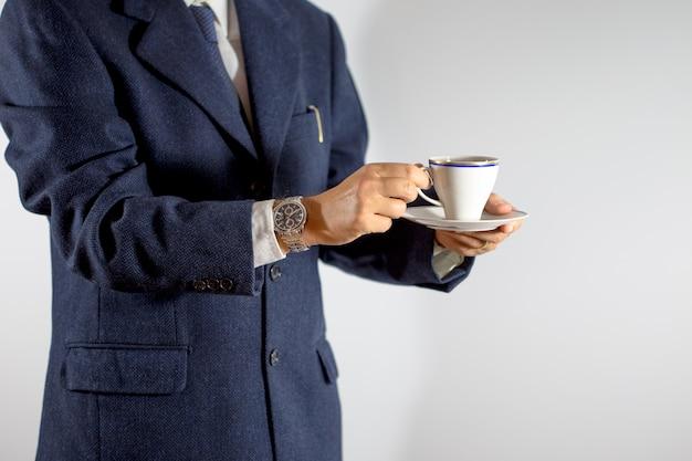 コーヒーや紅茶のカップを手で保持してエレガントな男