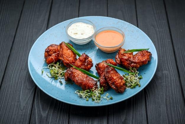 Запеченные куриные крылышки в азиатском стиле на тарелке