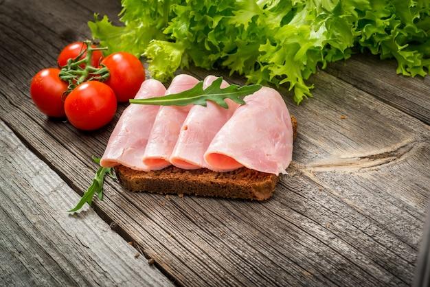 ハムと野菜のサンドイッチ。木製のテーブルのオーガニック製品