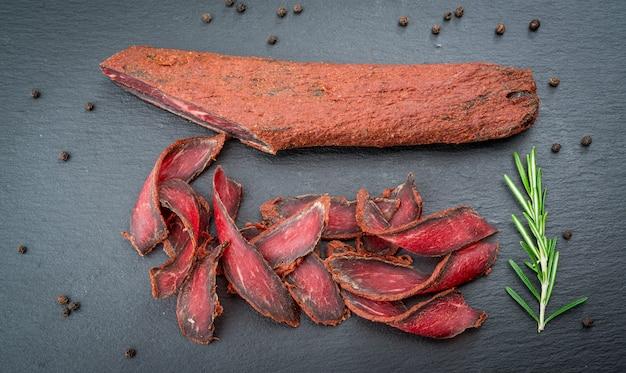 アルメニアのバストゥルマ。牛肉の塩漬けとスパイス。木製のテーブルのオーガニック製品
