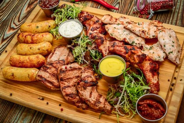 Ассорти вкусного жареного мяса и овощей со свежим салатом и соусом барбекю на разделочной доске на дровах