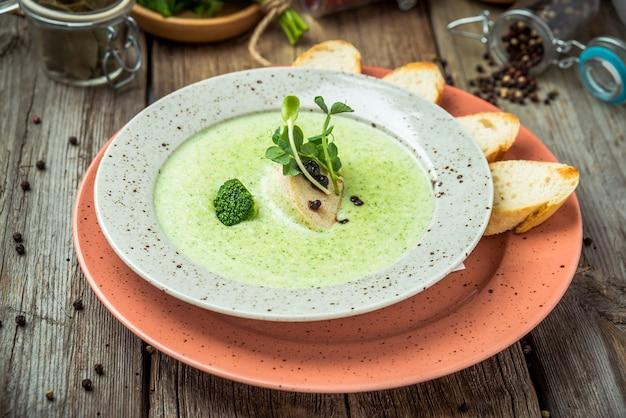 白い素朴なテーブル、トップビューでボウルにほうれん草のクリームスープ