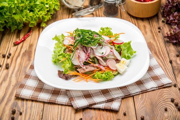 スパイシービーフスライスミートサラダ、ニンジン、トマト、キュウリ、パセリ、大根、葉ほうれん草、ロケット、古い木製のテーブルに赤いルビーフダンソウ