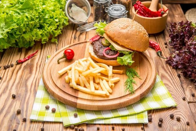 ファーストフード料理の上面図。クラフト紙とポテトチップスの肉バーガー。構図を奪います。