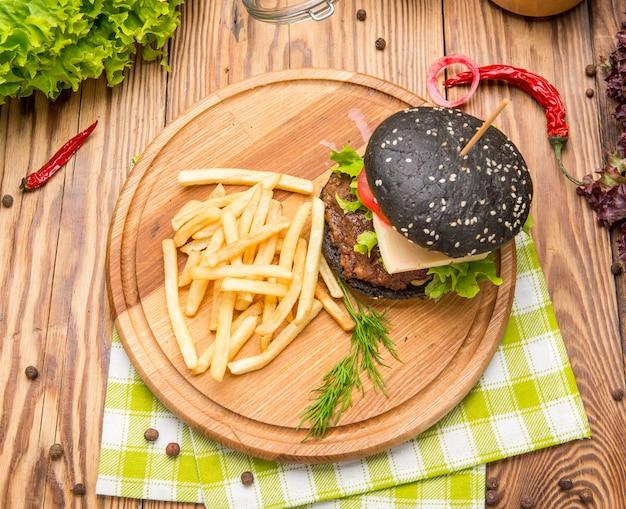 Изысканный черный бургер с острым соусом на деревянном столе