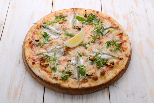 Вкусная острая итальянская еда, пицца с анчоусами и корнишонами, горячие пикантные блюда для гурмана