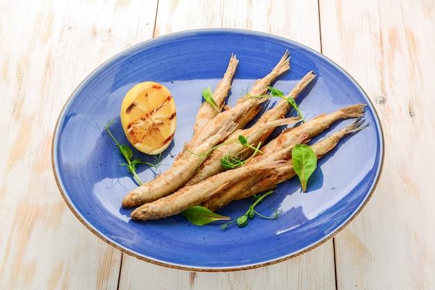 Деревянная доска с жареной рыбой и салатом
