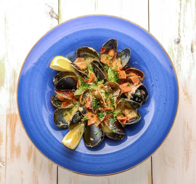 Вкусные свежеприготовленные черные мидии в томатном соусе в винтажной кастрюле с ложкой рядом с ломтиком лимона на деревянном фоне
