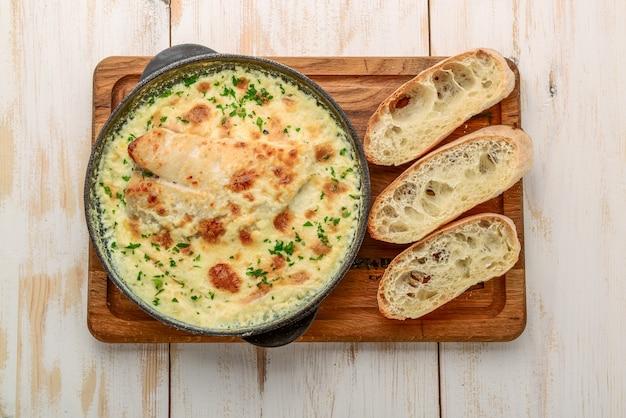 チーズ、サワークリーム、木製のテーブルにタマネギと白身魚のキャセロール