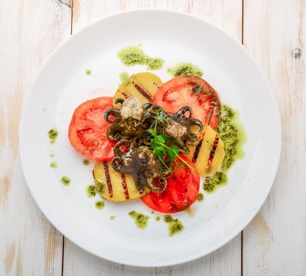 Осьминог на гриле на тарелке. осьминог на гриле с овощами гриль
