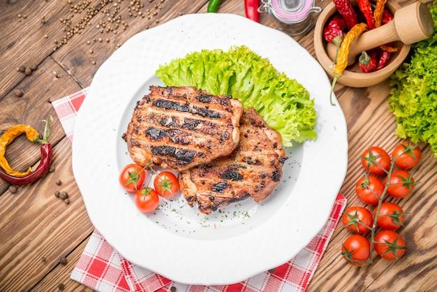 Жареная курица с зеленью подается на тарелке