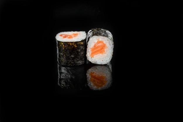 黒の背景に伝統的な新鮮な日本の寿司ロール