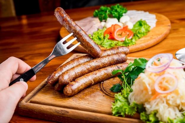 Жареная колбаса с квашеной капустой и горчичным соусом