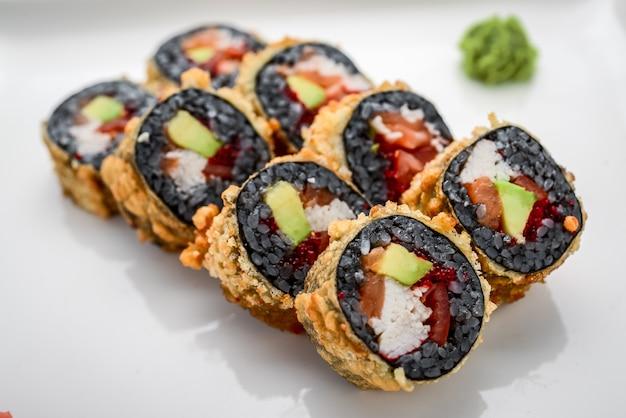 Суши ролл из свежего лосося, авокадо и сливочного сыра с черным рисом