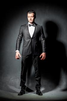 ボウタイと黒のスーツで自信を持ってハンサムな男の肖像