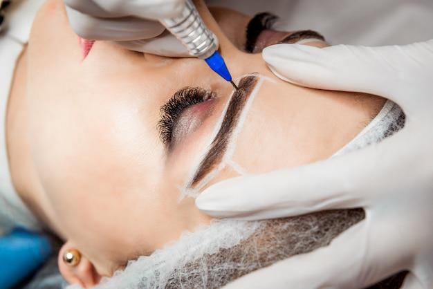 眉毛の永久化粧。ビューティーサロンで厚い眉を持つ美しい女性のクローズアップ。女性の顔の眉タトゥーを行う美容師。美容手順。