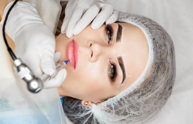 健康的なスパ。彼女の唇に恒久的な化粧タトゥーを持つ若い美しい女性