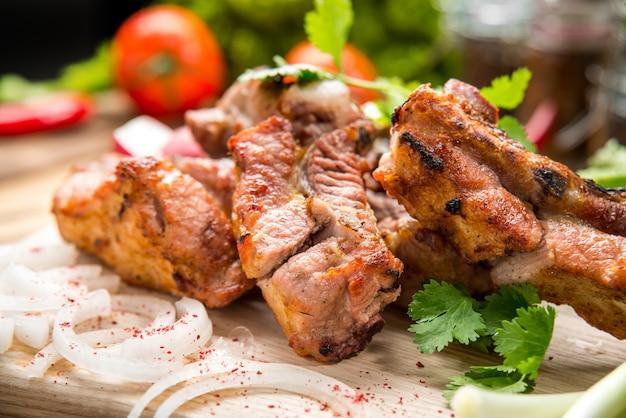 家族のバーベキューパーティーの白いプレートピクニックテーブルの上の野菜とおいしい焼き肉の盛り合わせ