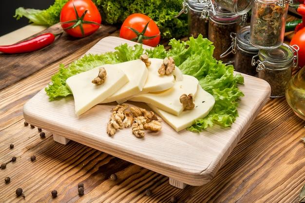 Домашний мягкий сыр сулугуни с помидорами, паприкой, луком и свежим базиликом на деревянной доске