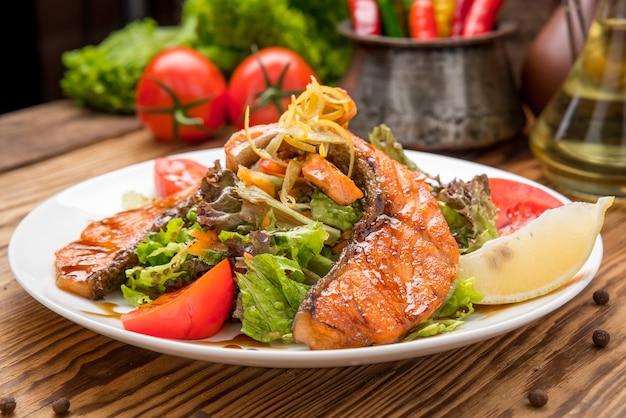 Стейк из лосося в белом блюде с овощами