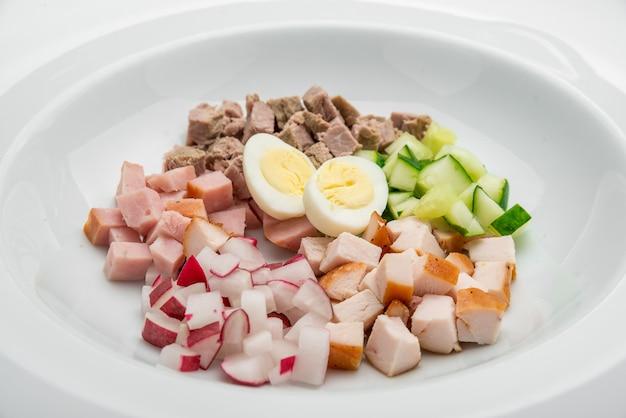 大根、キュウリ、木製のテーブルのディルと夏のヨーグルトの冷たいスープ。ロシアのオクローシカ。