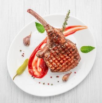骨のステーキ。白い木製のテーブルにトマホークステーキ。上面図。
