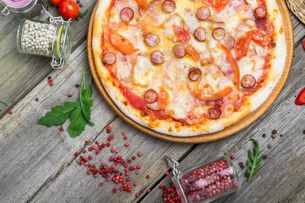 Пицца с помидорами, сыром моцарелла, маслинами и базиликом. очень вкусная итальянская пицца на деревянной доске для пиццы.
