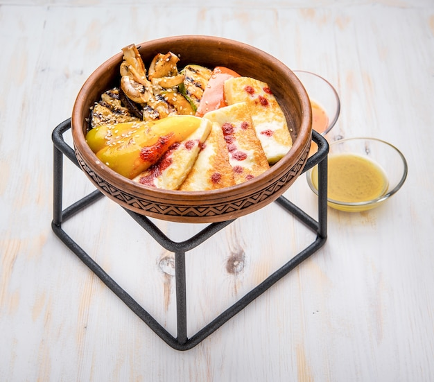 Сыр гриль с овощами гриль в глиняной тарелке