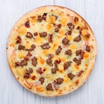 木の表面にひき肉トマト赤玉ねぎピザ