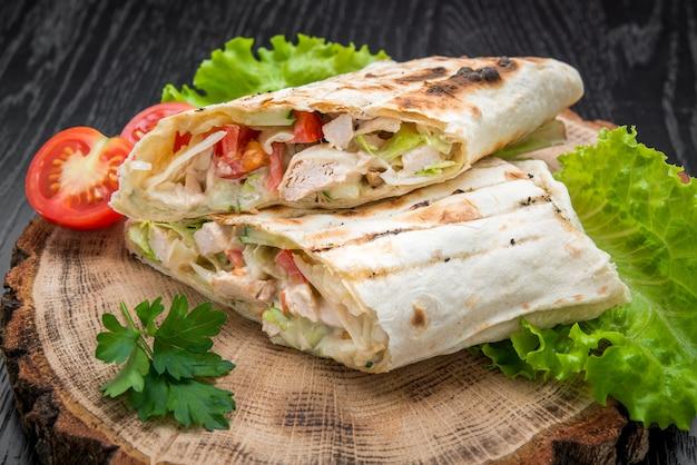 Тортилла обертывания с курицей-гриль или вегетарианская тартель из свежих овощей на деревянном фоне