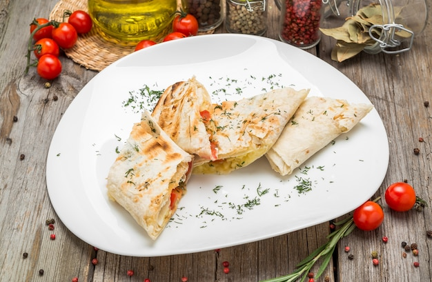 Бутерброд с шаурмой со свежими овощами и соусом на серой тарелке, украшенный помидорами черри, листьями базилика на сером столе