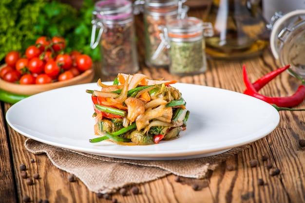 Оливковое масло льется в тарелку с салатом
