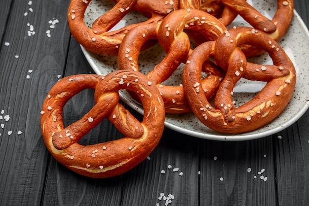 Свежие баварские крендели на деревянном столе, крендель с солью