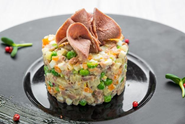 健康的な自家製ロシアの伝統的なサラダオリビエプレートで食べる準備ができて、クローズアップ