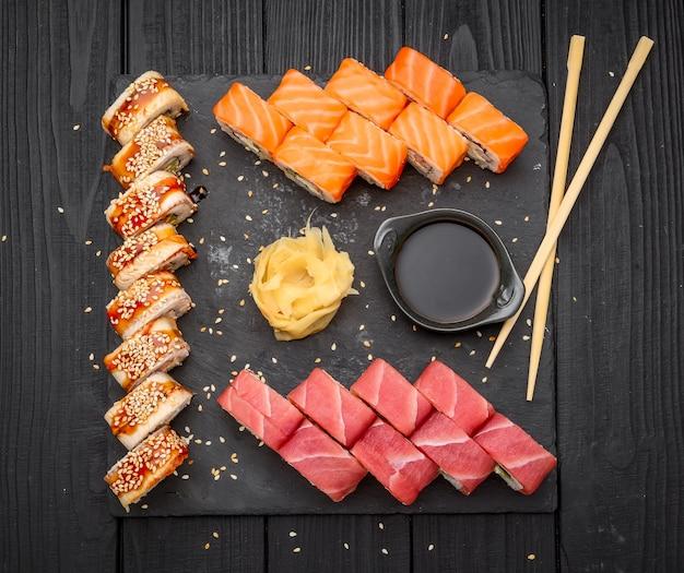 Суши-сет нигири и суши-роллы подаются на черном каменном сланце