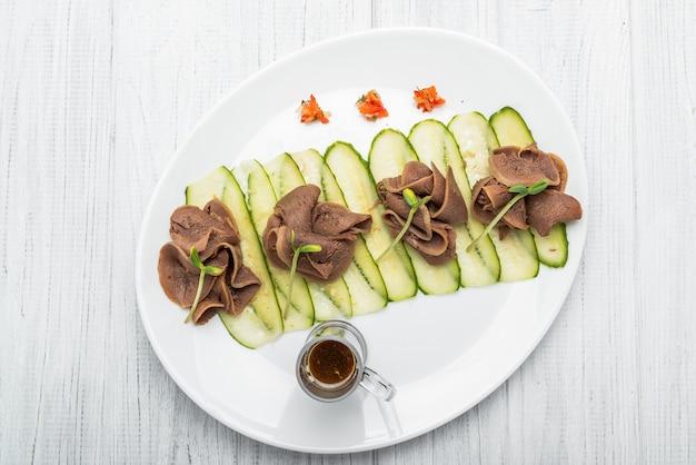 ペストとサラダと暗い木製のテーブルにゆでた牛タン