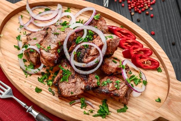 家族のバーベキューパーティーのための白いプレートピクニックテーブルの上の野菜とおいしい焼き肉の盛り合わせ