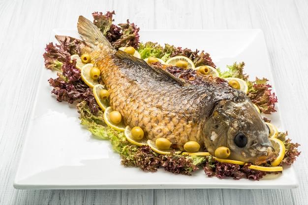 魚のレタスの葉と大きな銀の燭台のテーブルの上