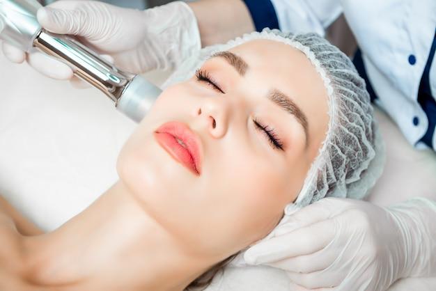 美容師は、美容院の美しい若い女性の顔の皮膚のしわを引き締めて滑らかにするための若返りフェイシャル注射手順を行います