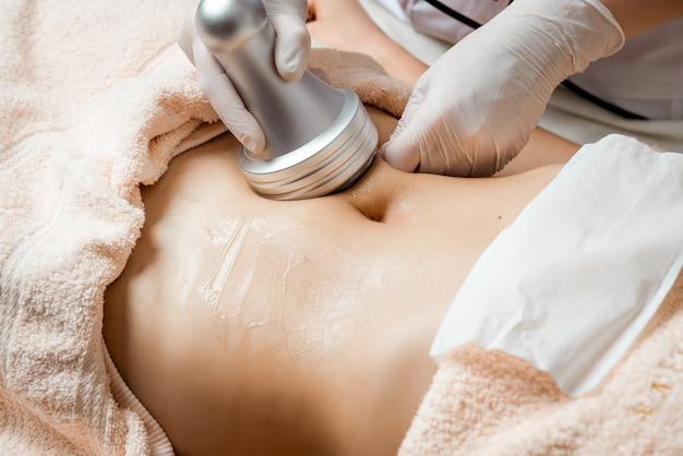 ハードウェア美容。ボディケア。スパでのトリートメント。超音波キャビテーションボディコンタートリートメント。美容室で抗セルライトと抗脂肪療法を受ける女性。
