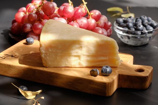 グレープベリーと木製のカットボードにパルミジャーノチーズ