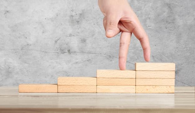 Человек, похожий на руку, шагает вверх по деревянным блокам