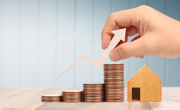 木のおもちゃの家の住宅ローンのプロパティホームコンセプト家族、コインを手に購入